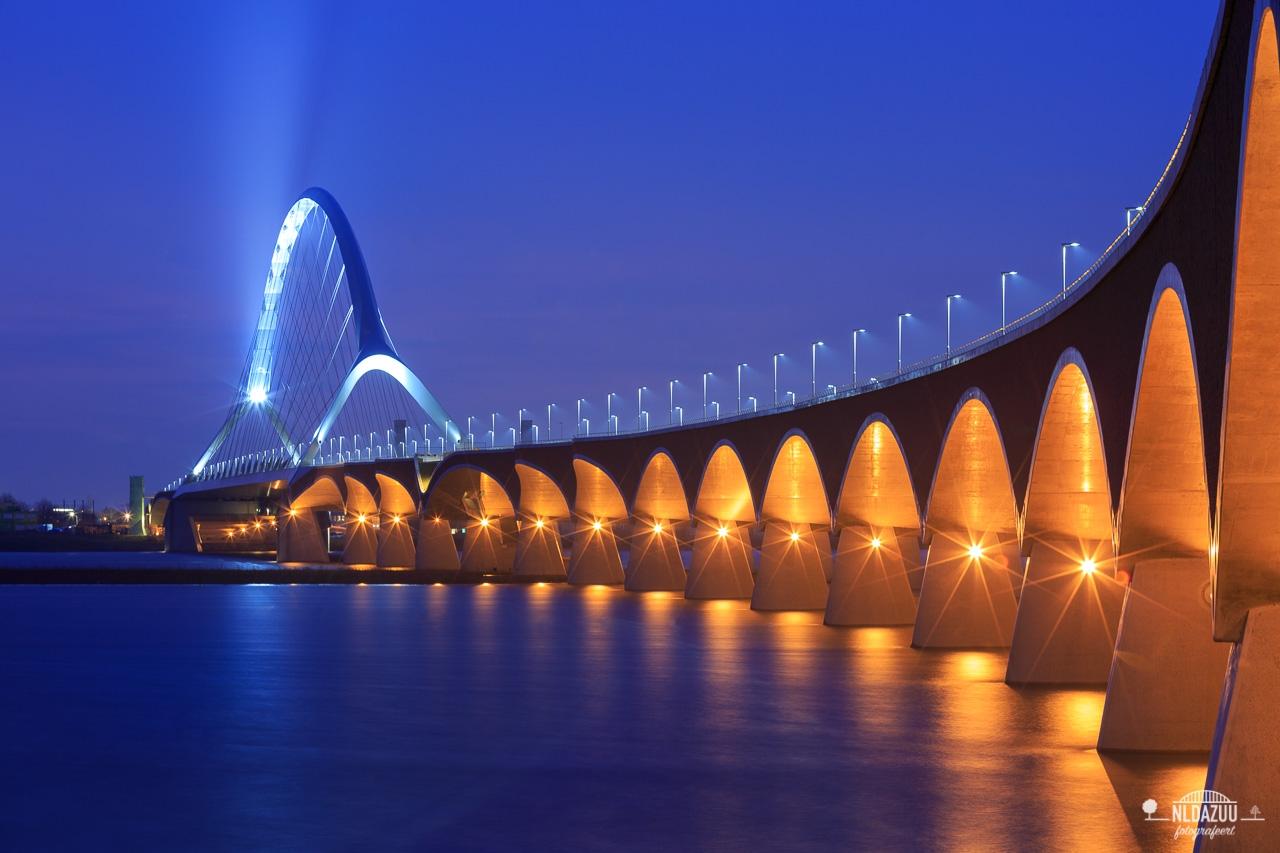 Nijmeegse Waalbrug de Oversteek in het blauwe uur met Hoogwater